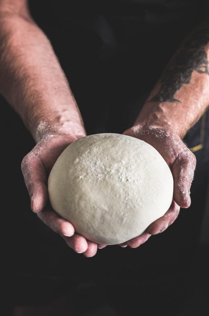 Person holding a ball of dough on a dark background